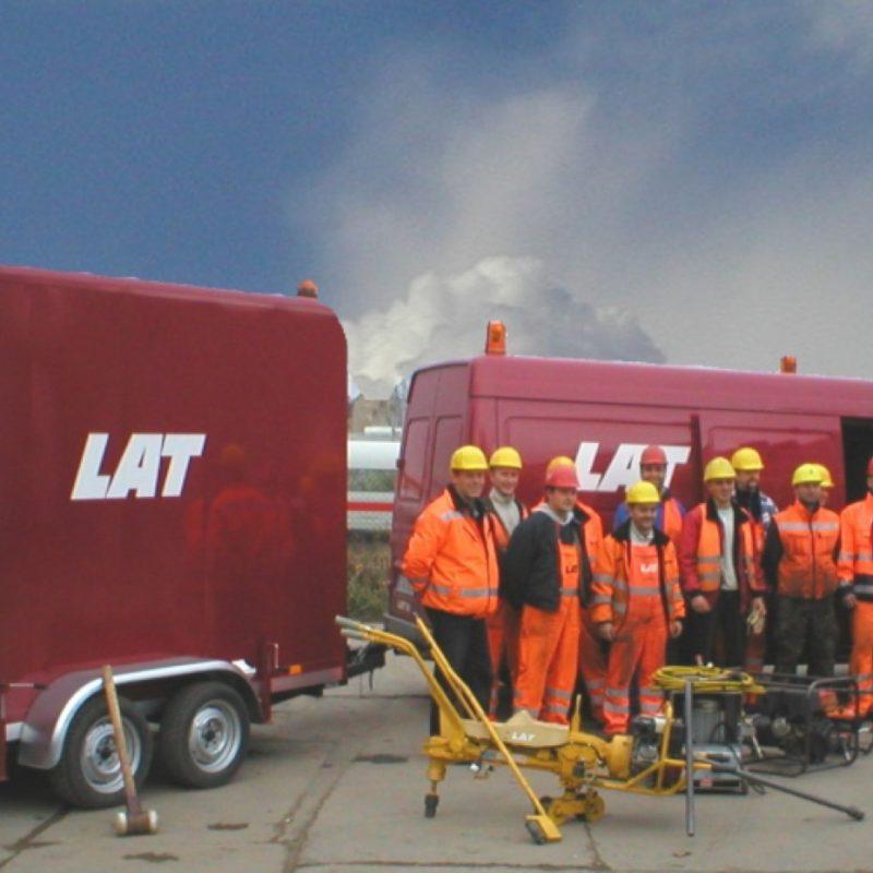 Geschichte der LAT-Gruppe - LAT Mitarbeiter posieren vor LAT Dienstwagen, ICE der Deutschen Bahn im Hintergrund.