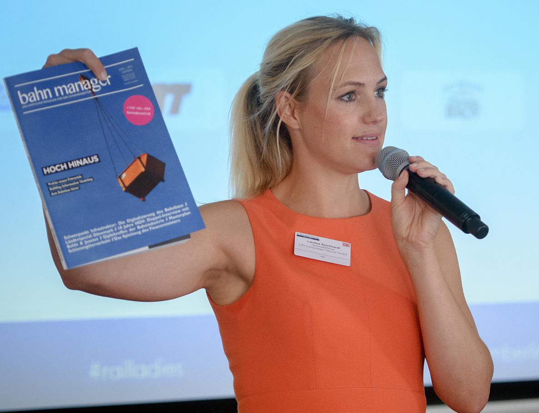 LAT Aktuell - Geschäftsführerin Larissa Zeichhardt ein Mikrophon und zeigt eine Zeitschrift mit der Aufschrift