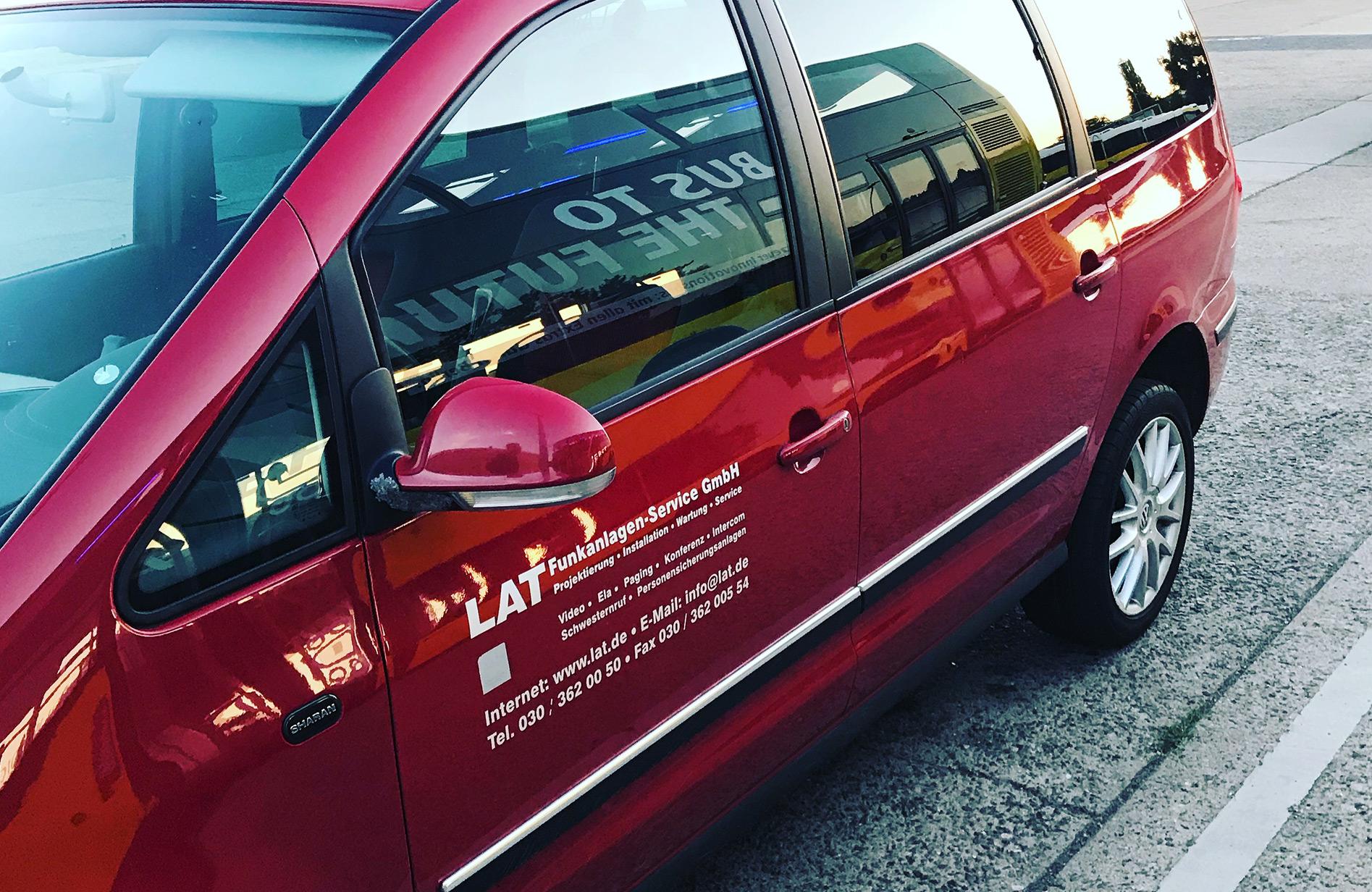 Im Fenster eines LAT Autos der Funkanlagen-Service GmbH spiegelt sich der Schriftzug des Innovationsbusses