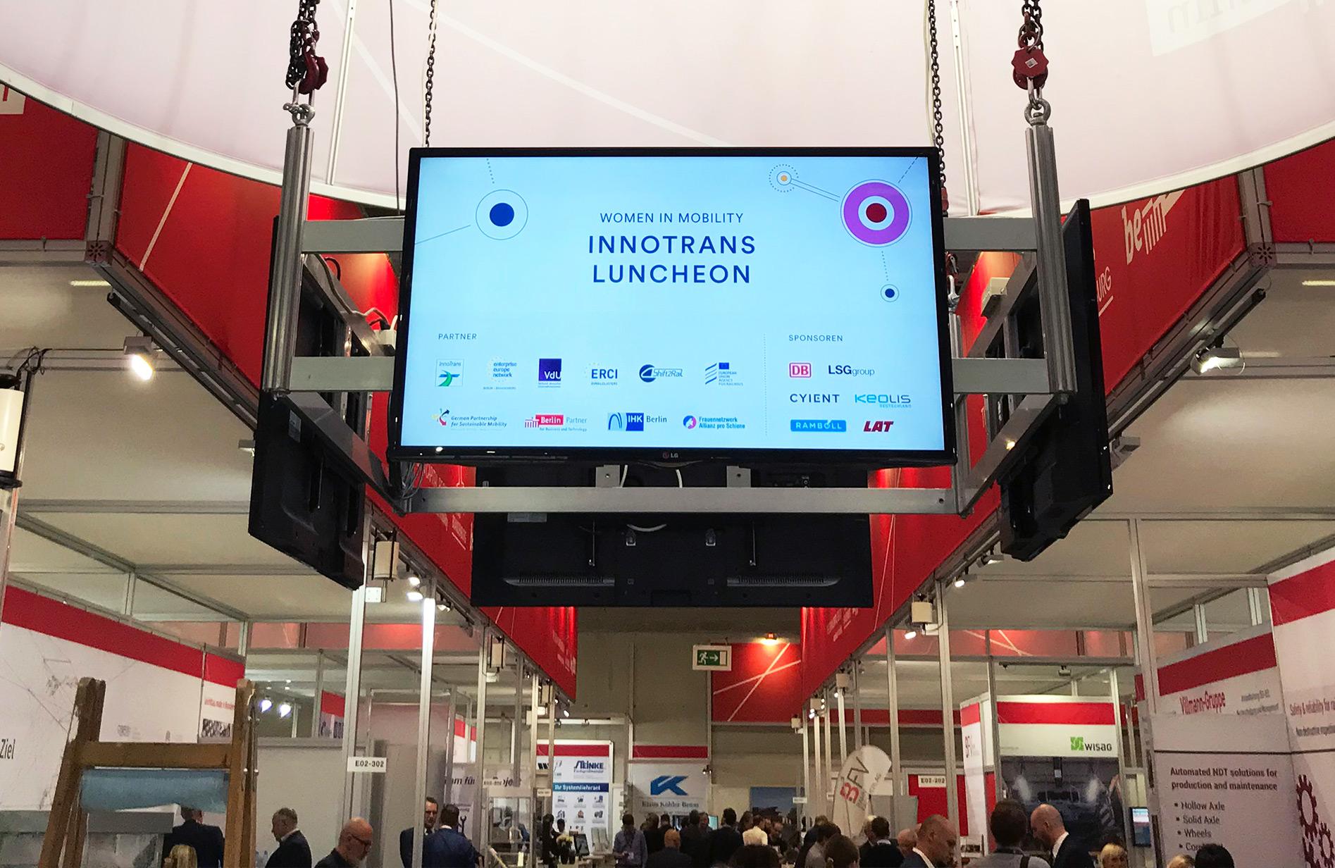 Gleichberechtigt & digitalisiert in die Zukunft - Bildschirm zeigt auf einer Messe den Schriftzug vom InnoTrans Ladies Lunch